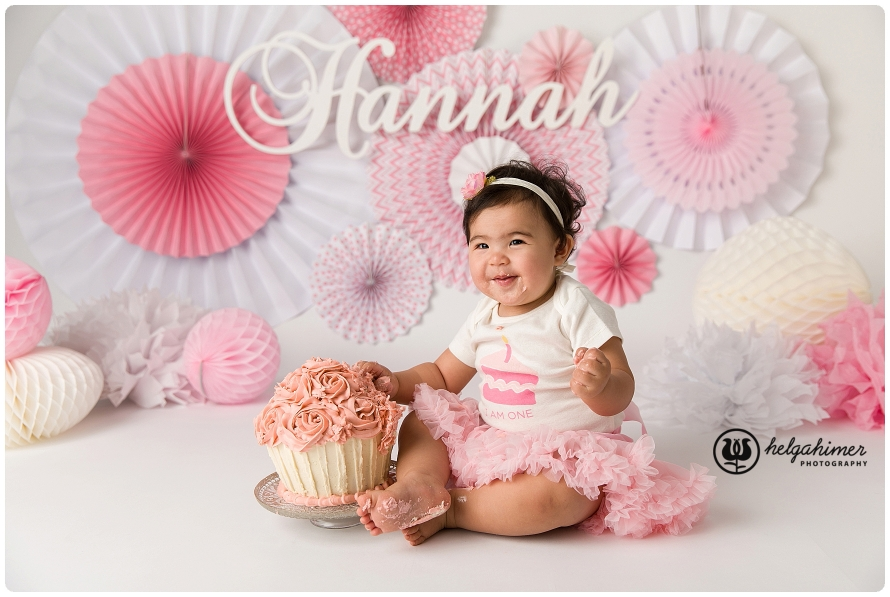 cake smash session for a chines little girl in pink, the background have pinwheels and she is wearing a pink tutu